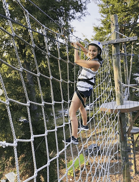 woman climbing a rope obstacle at Wild Blue Ropes in Charleston, SC